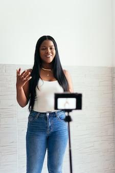 Mujer africana se graba a sí misma con su cámara en casa
