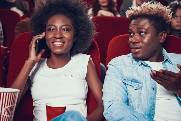 Mujer africana habla en voz alta por teléfono durante la película