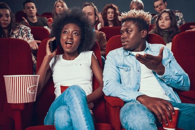 Mujer africana habla en voz alta por teléfono durante el show de cine