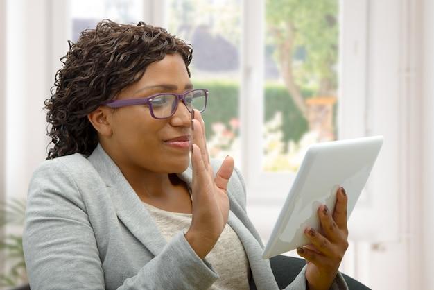 Mujer africana hablando en línea con tableta