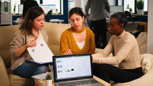 Mujer africana hablando de proyecto, discutiendo ideas de puesta en marcha usando pc, empleados diversos reunidos en co-working, proceso de trabajo en empresa ocupada. concepto de ayuda de trabajo en equipo