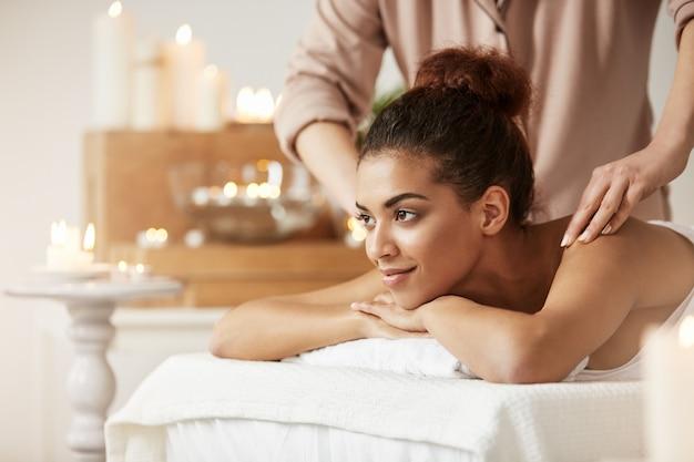 Mujer africana hermosa que sonríe disfrutando de masaje en balneario.