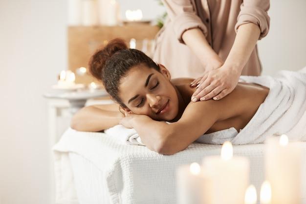 Mujer africana hermosa que sonríe disfrutando de masaje con los ojos cerrados en salón del balneario.