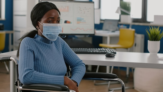 Mujer africana inmovilizada en silla de ruedas con aspecto perdido en una nueva oficina normal