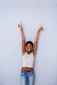 Mujer africana joven emocionada que señala para arriba en fondo gris