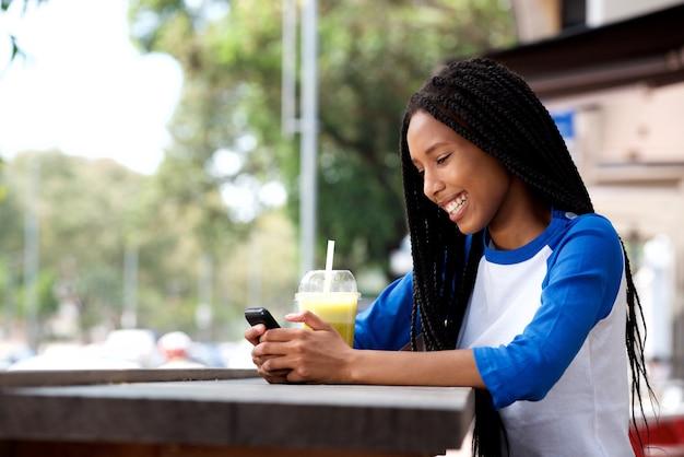 Mujer africana joven feliz que se sienta en el café al aire libre usando el teléfono móvil