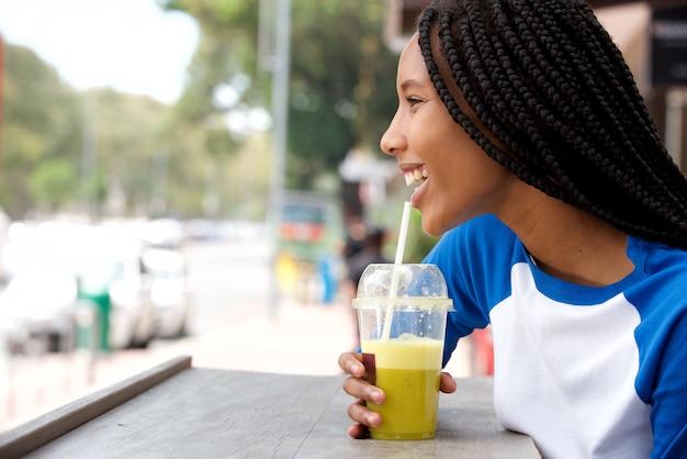 Mujer africana joven con el pelo trenzado que sorbe el jugo en el café