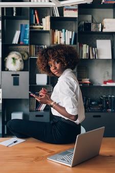 Mujer africana joven que presenta en oficina moderna con smartphone y que mira la cámara