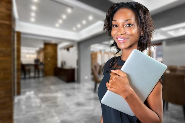Mujer africana joven que sostiene el ordenador portátil gris