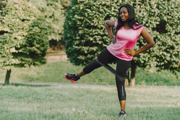 Mujer africana joven sana al aire libre en la mañana. chica con goma de borrar.