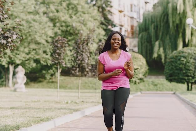 Mujer africana joven sana al aire libre en la mañana. mujer en camiseta rosa.