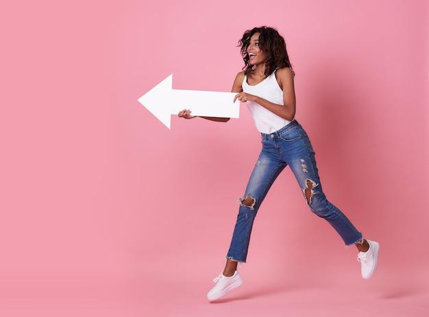 Mujer africana joven sorprendida saltando con su flecha apuntando al espacio de copia aislado sobre banner rosa.