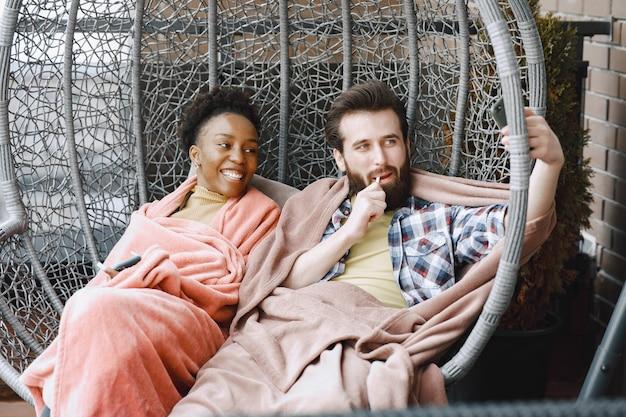 Mujer africana con marido. chico y chica con cuadros escoceses. amantes tomando café en el balcón.