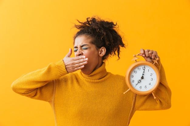 Mujer africana molesta vistiendo suéter que se encuentran aisladas, sosteniendo el despertador, bostezando