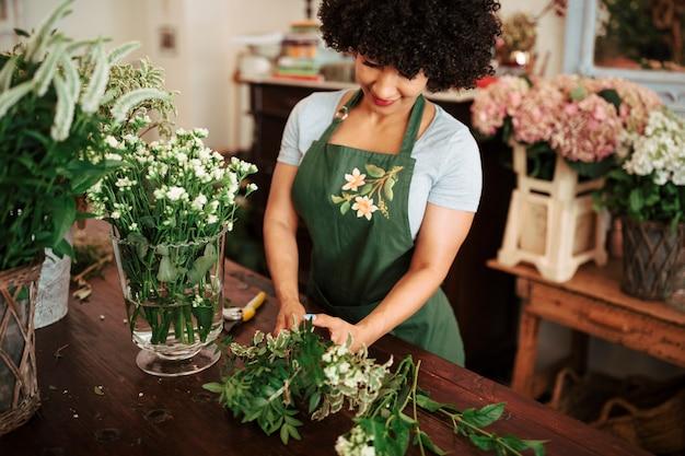 Mujer africana que clasifica las plantas en el escritorio de madera