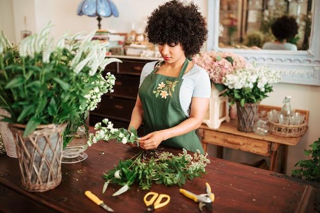 Mujer africana que clasifica las plantas de la flor en el escritorio de madera