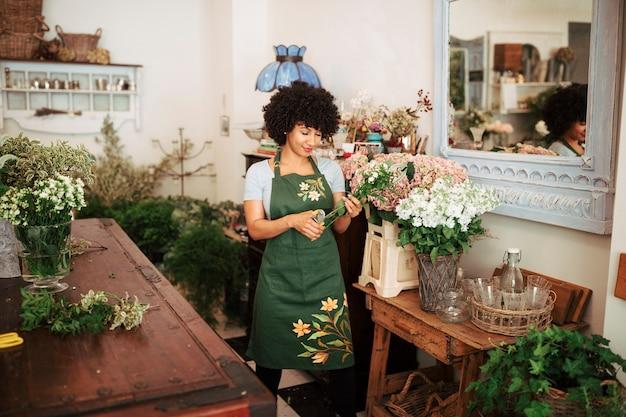 Mujer africana que corta el vástago de flores