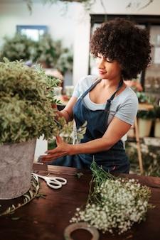 Mujer africana que cuida la planta en la tienda