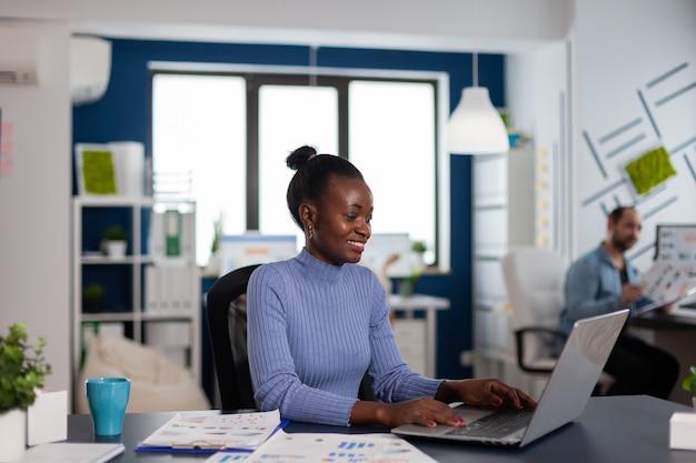 Mujer africana que trabaja escribiendo en la computadora portátil, concentrada para terminar el plazo importante