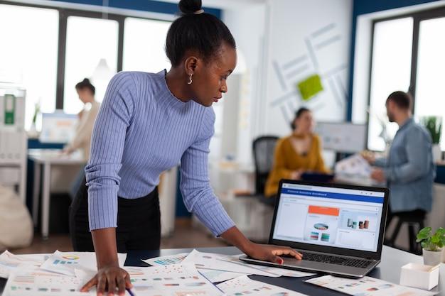 Mujer africana scorlling en portátil mirando concentrado en gráficos y colegas multiétnicos que trabajan en marketing. equipo diverso de gente de negocios que analiza los informes financieros de la empresa desde la computadora.