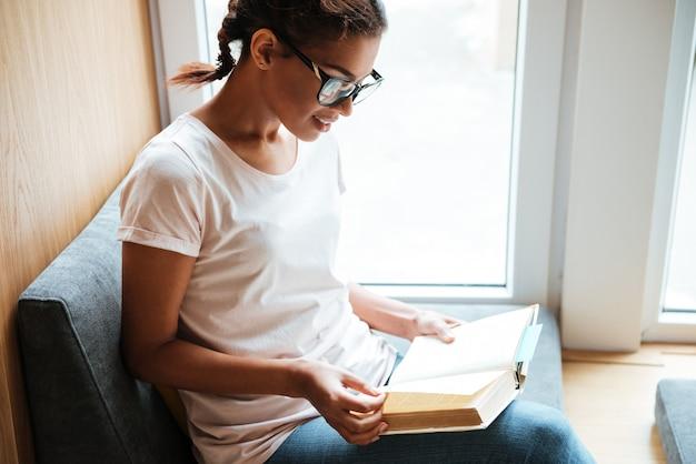 Mujer africana sentada en la biblioteca y leer libros.