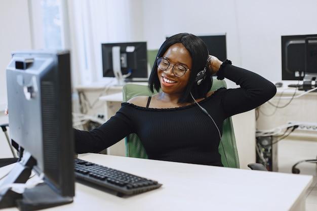 Mujer africana sentada en la clase de informática. señora con gafas. estudiante sentado en la computadora.