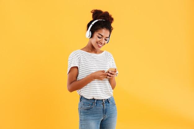 Mujer africana sonriente escuchando música y usando el teléfono