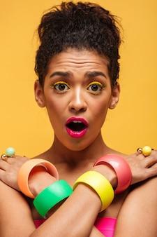Mujer africana sorprendida vertical en coloridos adornos con la boca abierta mirando a la cámara cruzando las manos sobre los hombros, sobre la pared amarilla