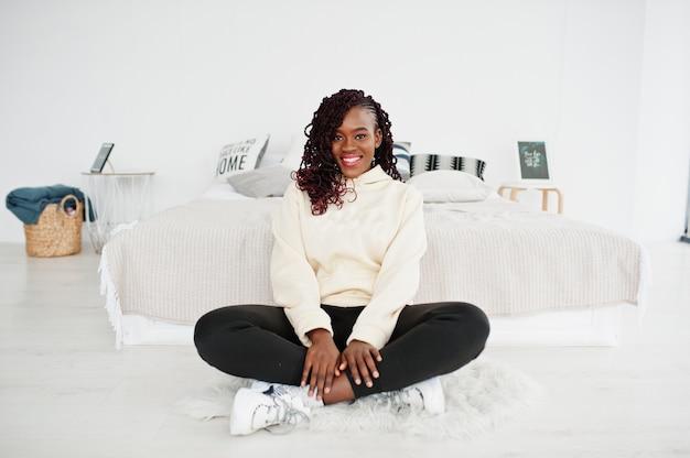 Mujer africana en sudadera con capucha sentarse cerca de la cama en casa