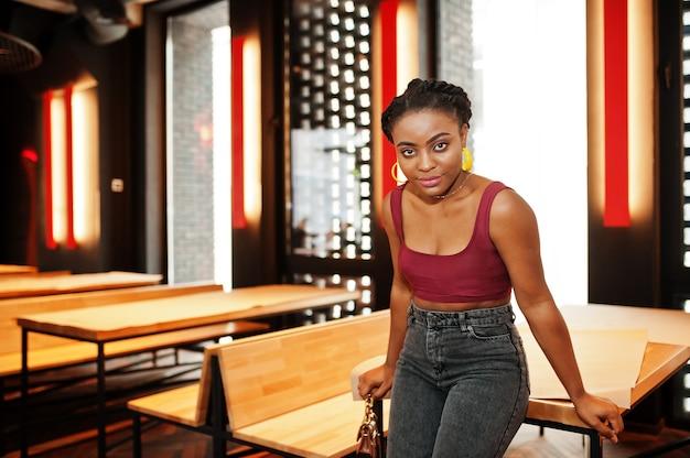 Mujer africana en top rojo marsala y jeans plantean interior.