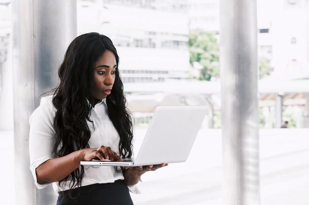 Mujer africana trabajando en la computadora portátil