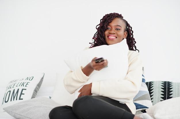 Mujer africana viendo la televisión en casa y sosteniendo un control remoto en la cama