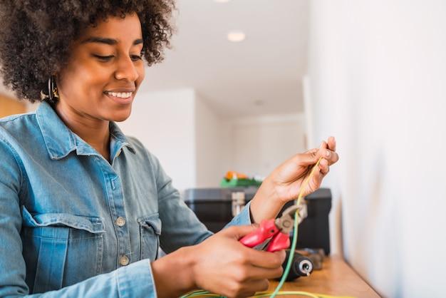 Mujer afro arreglando el problema de electricidad en el hogar.