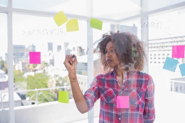 Mujer con afro dibujando en diagrama de flujo con marcador