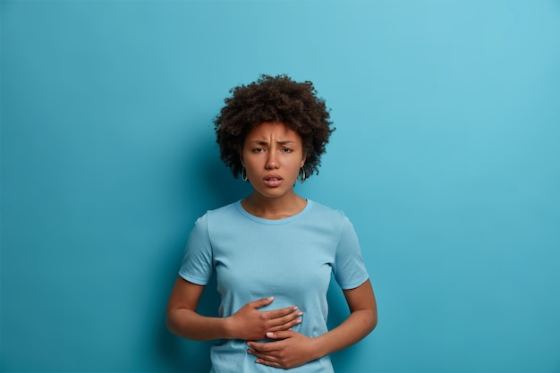 Mujer afro disgustada siente malestar en el estómago, mantiene las palmas en la barriga, tiene calambres menstruales, usa camiseta informal, comió alimentos en mal estado, aislado en la pared azul, expresa emociones negativas con mímica