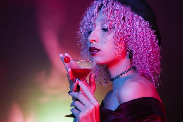 Mujer afro étnica bebiendo un cóctel rojo de halloween con una cereza