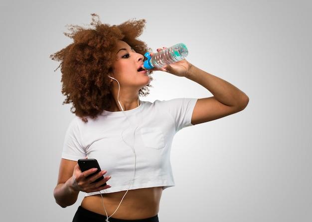Mujer afro de fitness joven sosteniendo un móvil y agua potable al mismo tiempo