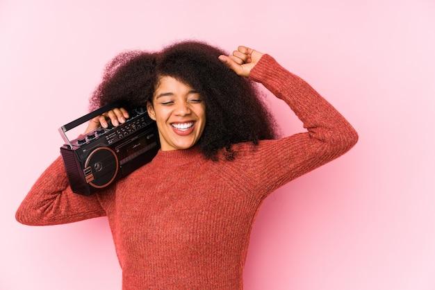 La mujer afro joven que sostenía un cassete aisló levantar el puño después de una victoria, concepto del ganador.