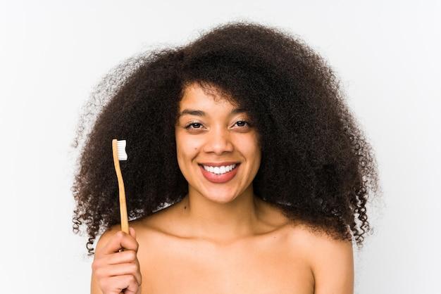 La mujer afro joven que sostenía un cepillo de dientes aisló feliz, sonriente y alegre.