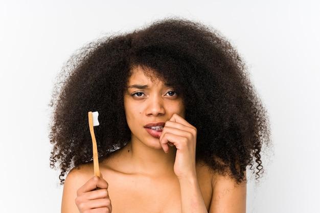 La mujer afro joven que sostiene un cepillo de dientes aisló morderse las uñas, nervioso y muy ansioso.