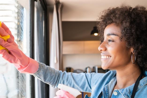 Mujer afro limpieza ventana con un trapo en casa.
