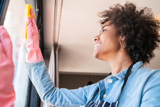 Mujer afro limpieza ventana con trapo en casa.