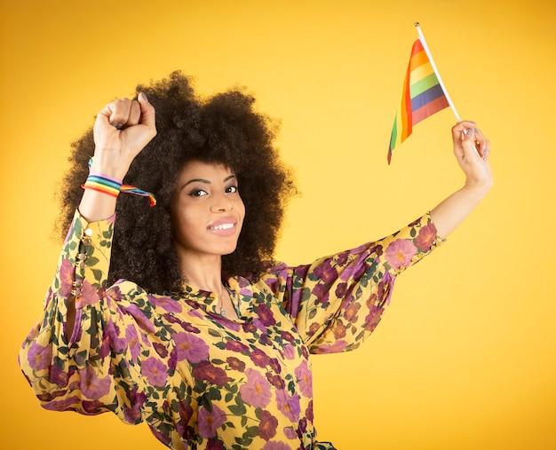 Mujer afro mixta con bandera del orgullo gay, grita por sus derechos, sobre fondo amarillo