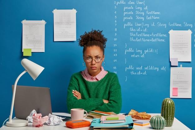 Mujer afro molesta se ve con expresión sombría, posa en un espacio de coworking, crea su propia startup basada en pronósticos innovadores, usa el bloc de notas para escribir información