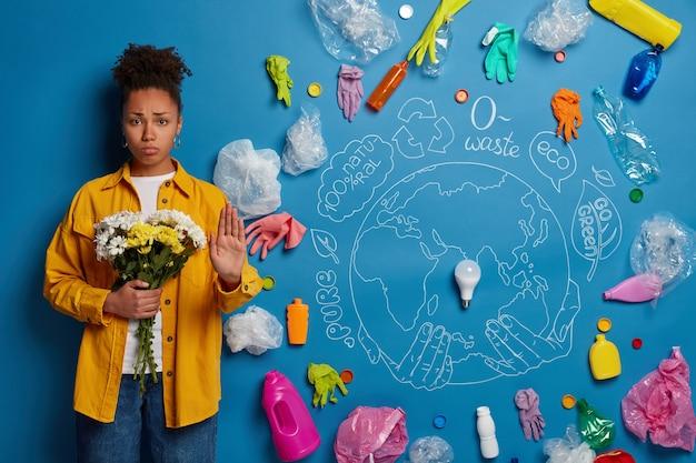 Mujer afro de pelo rizado insatisfecha hace un gesto de parada, sostiene flores en las manos, pide a la humanidad que se detenga y piense en limpiar la naturaleza