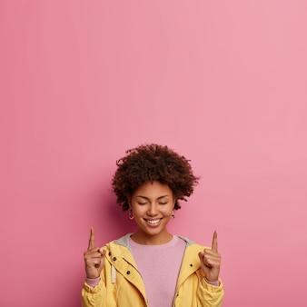 La mujer afro positiva apunta arriba con los ojos cerrados, se siente feliz de participar en la campaña publicitaria, tiene una sonrisa suave y dentuda