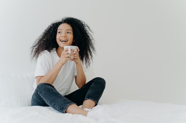 La mujer afro positiva sostiene una taza de café, se sienta en la cama, mira alegremente a un lado, disfruta del buen tiempo