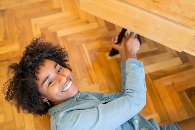 Mujer afro reparando muebles en casa.
