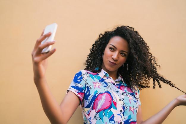 Mujer afro tomando selfies con teléfono.