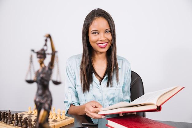 Mujer afroamericana alegre con el libro en la mesa con teléfono inteligente, estatua y ajedrez